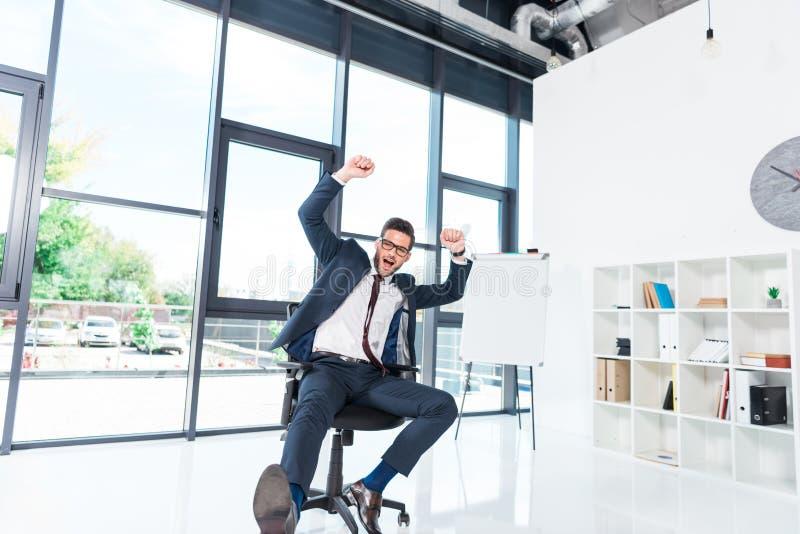 aufgeregter junger Geschäftsmann, der Hände beim Sitzen auf Stuhl triumphiert und anhebt lizenzfreie stockbilder
