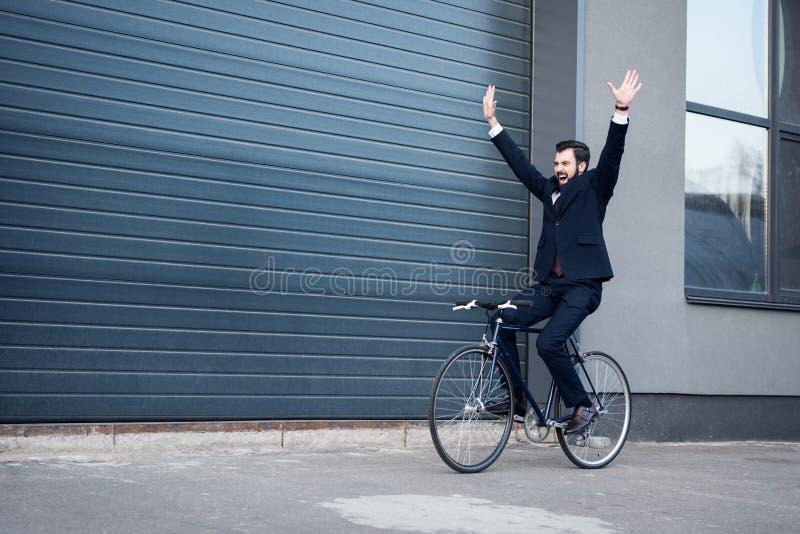aufgeregter junger Geschäftsmann mit den ausgestreckten Armen, die Fahrrad fahren stockfotos
