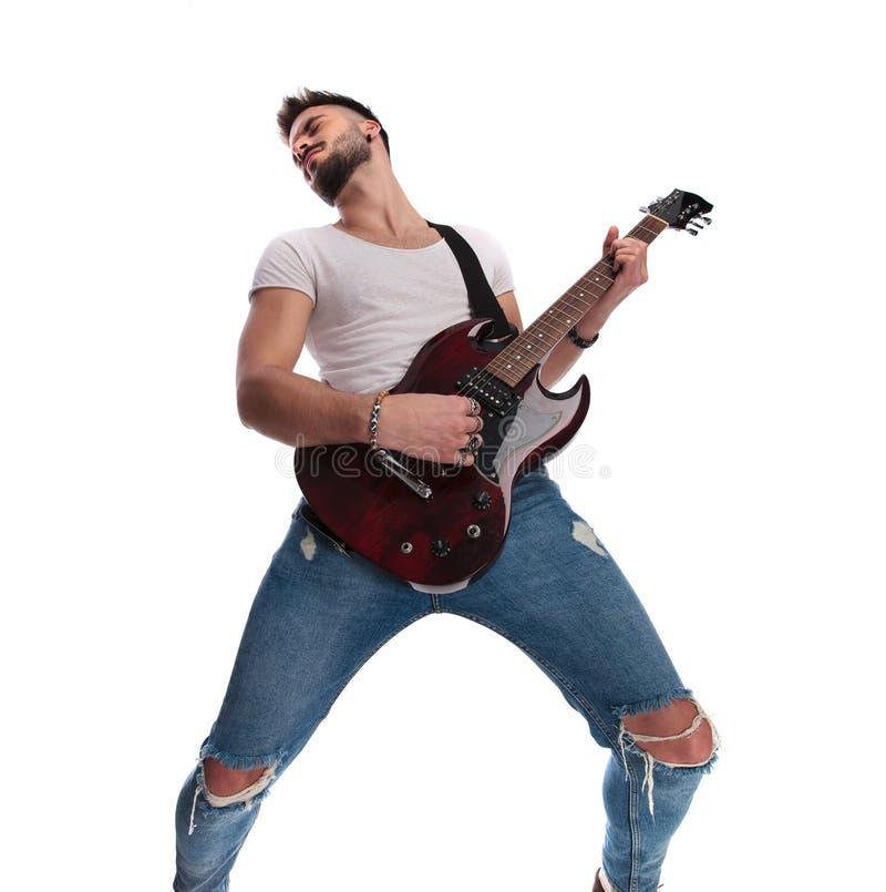 Aufgeregter junger Gitarrist, der die Gitarre spielt und sich zurück lehnt stockfotos