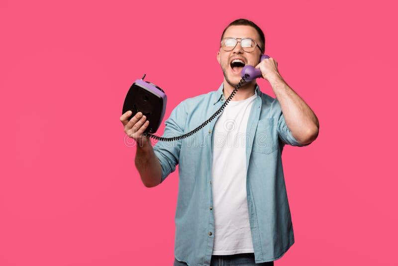 aufgeregter junger Mann in den Brillen sprechend per das Weinlesetelefon lokalisiert lizenzfreies stockbild