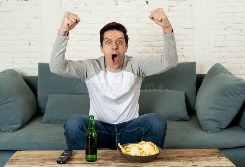 Aufgeregter junger Mann, der auf dem aufpassenden Fußball der Couch sitzt Sportanhänger- und -fankonzept stockfoto