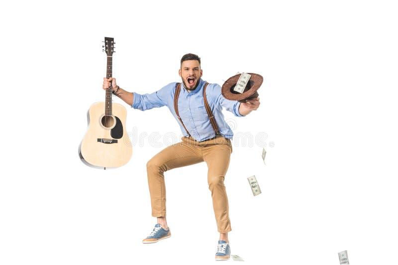 aufgeregter junger Mann, der Gitarre und Hut mit Dollarbanknoten hält lizenzfreie stockbilder