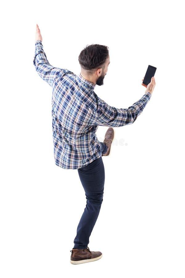 Aufgeregter junger Mann, der Handylesemitteilung auf dem leeren Bildschirm rückwärts fällt blockiert lizenzfreies stockbild