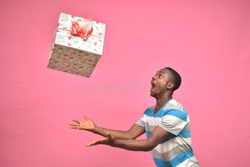 aufgeregter junger Mann, der mit einem Fanggeschenk-Kasten aufwartet lizenzfreie stockbilder