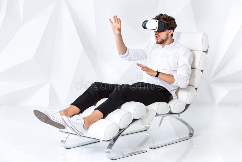 Aufgeregter junger Mann erhält Erfahrung unter Verwendung der VR-Kopfhörergläser virtueller Realität gestikulierend mit seinen Hä lizenzfreie stockfotografie