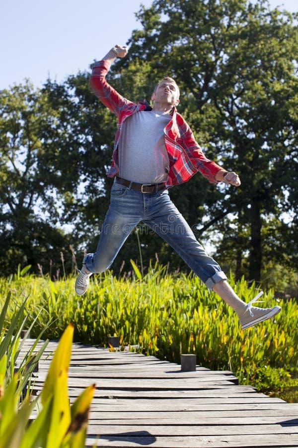 Aufgeregter junger Mann hoch, der zum Spaß in grünen Park springt stockfotos