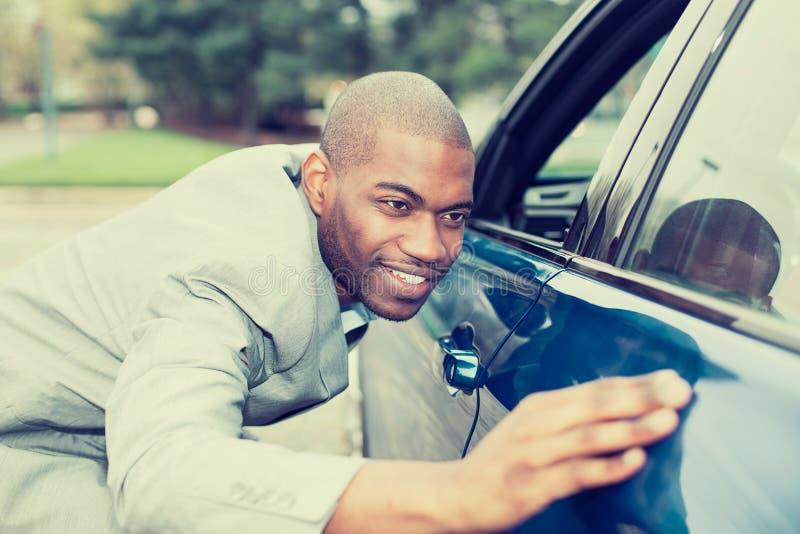 Aufgeregter junger Mann und sein Neuwagen stockfoto