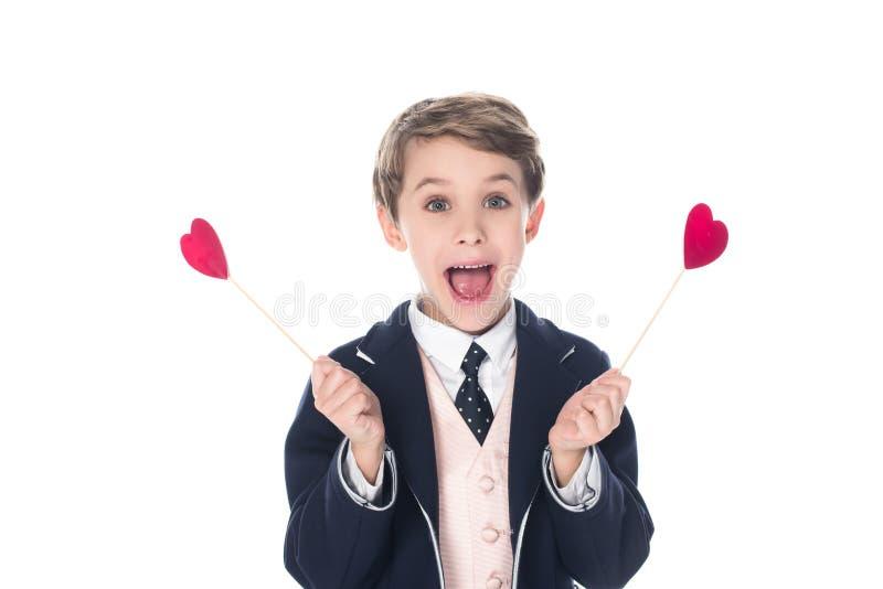 aufgeregter kleiner Junge, der Herzen auf Stöcken hält und an der Kamera lächelt stockbilder