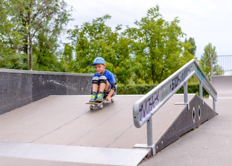 Aufgeregter kleiner Junge, der sein neues Skateboard ausprobiert stockbilder