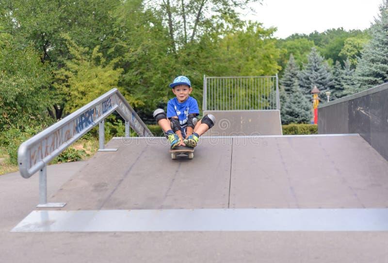 Aufgeregter kleiner Junge, der sein neues Skateboard ausprobiert stockfotos