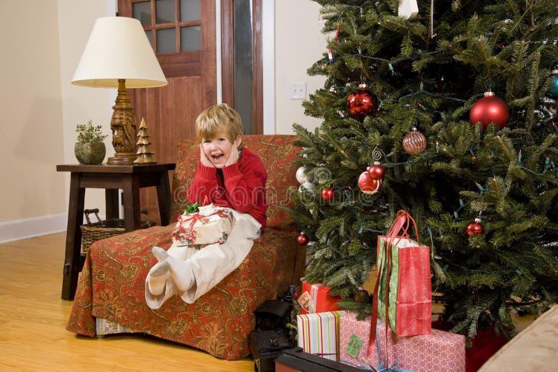 Aufgeregter kleiner Junge mit Geschenk durch Weihnachtsbaum lizenzfreie stockfotos