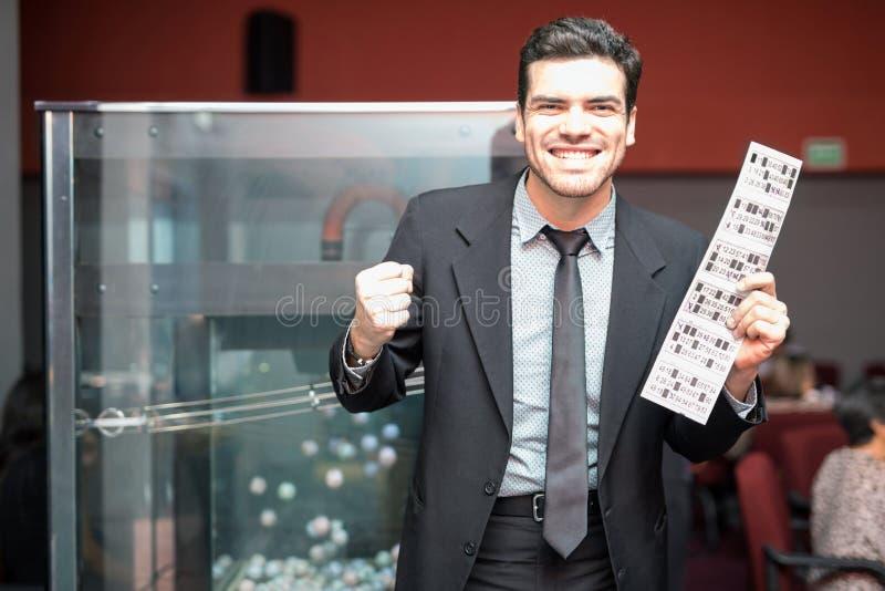 Aufgeregter Mann, der ein Lotteriespiel gewinnt lizenzfreies stockbild