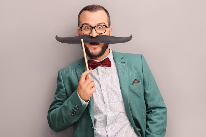Aufgeregter Mann, der einen gefälschten Schnurrbart auf seinem Gesicht hält lizenzfreie stockfotografie