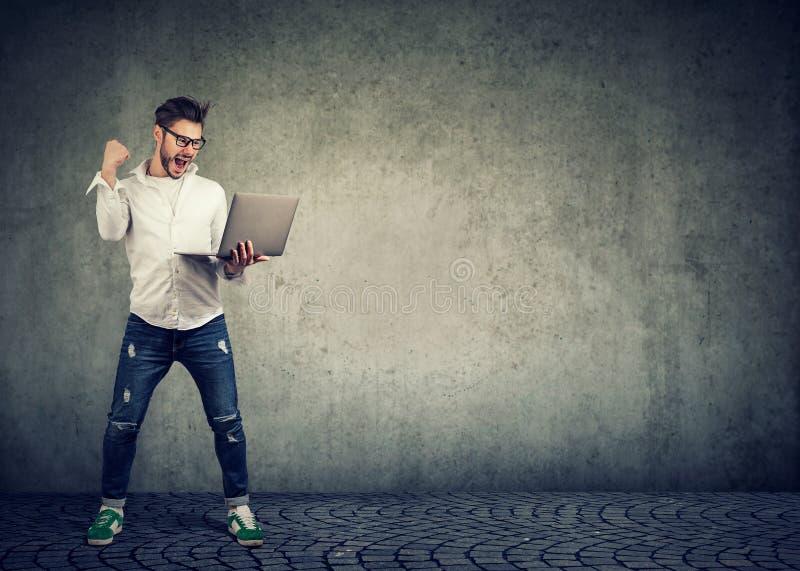 Aufgeregter Mann, der Gewinn unter Verwendung des Laptops feiert stockbild