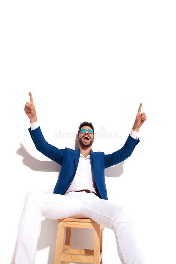 Aufgeregter Mann, der mit den oben zeigenden und schreienden Händen sitzt stockfotografie