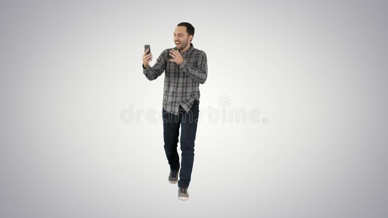 Aufgeregter Mann unter Verwendung Smartphonenotierenden Videoblog vlog auf Steigungshintergrund stockbild