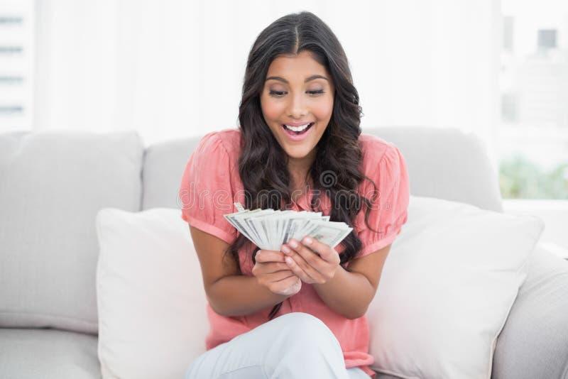 Aufgeregter netter Brunette, der auf der Couch hält Geld sitzt lizenzfreie stockfotos