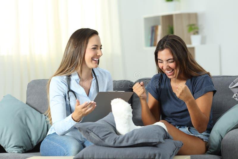 Aufgeregter Patient, der gute Nachrichten von einem Doktor empfängt stockfoto