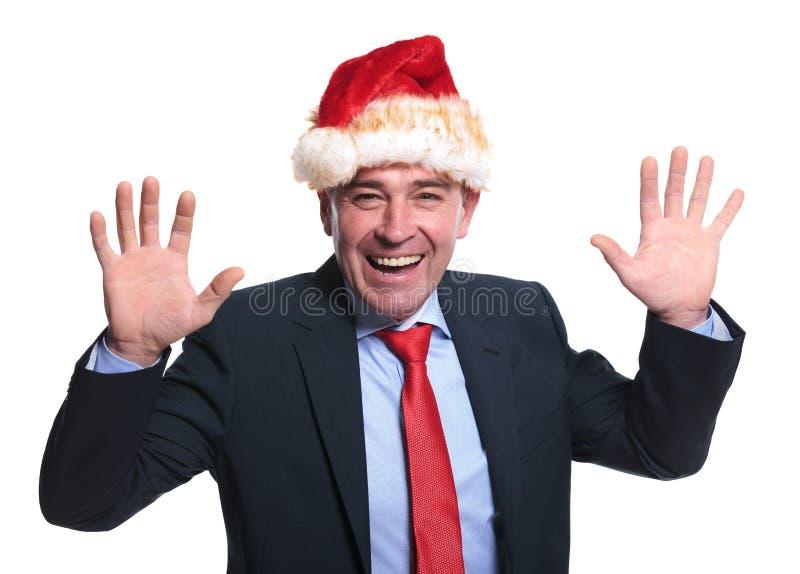 Aufgeregter reifer Geschäftsmann, der einen Weihnachtsmann-Hut trägt lizenzfreie stockfotos