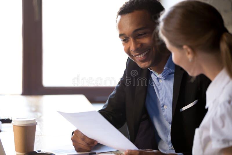 Aufgeregter schwarzer Arbeitgeber las Bewerberzusammenfassung am Interview lizenzfreie stockfotografie