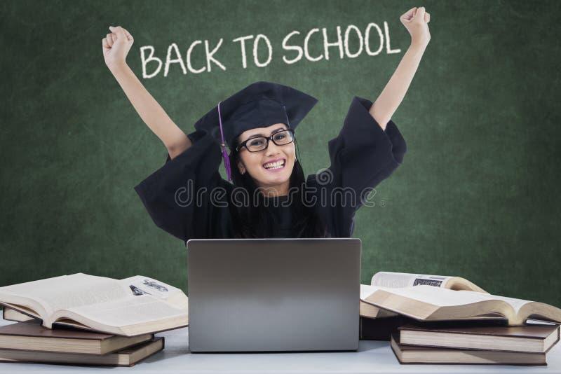 Aufgeregter Student mit Doktorhut zurück zu Schule stockfotografie