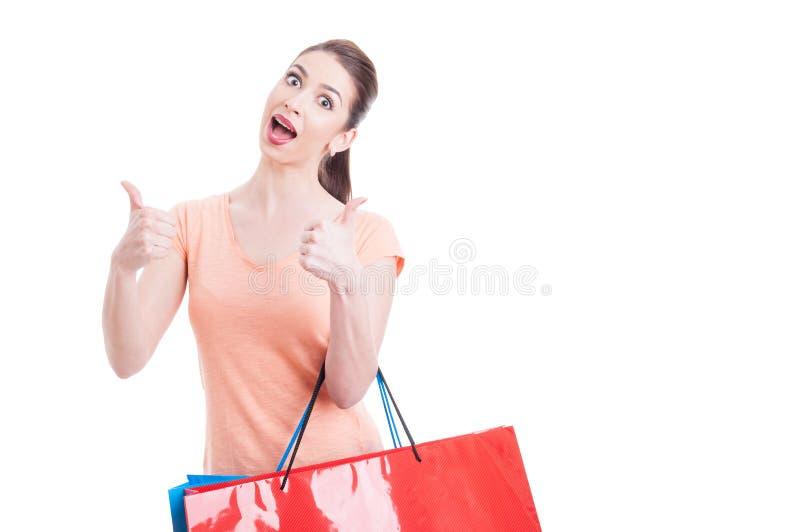 Aufgeregter weiblicher Käufer, der Daumen-oben zeigt stockfotografie