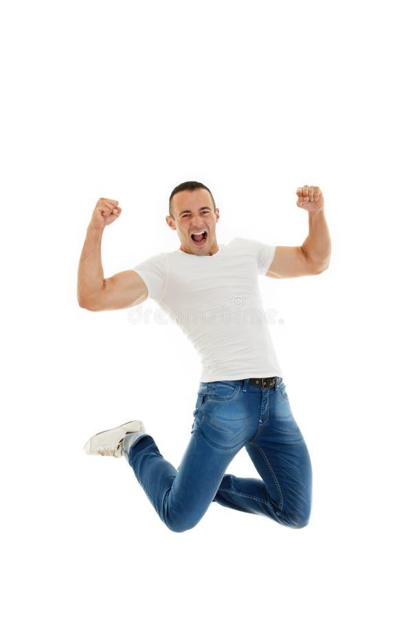 Aufgeregter zufälliger junger kaukasischer Mann, der seine Fäuste und jumpi zusammenpreßt stockfoto
