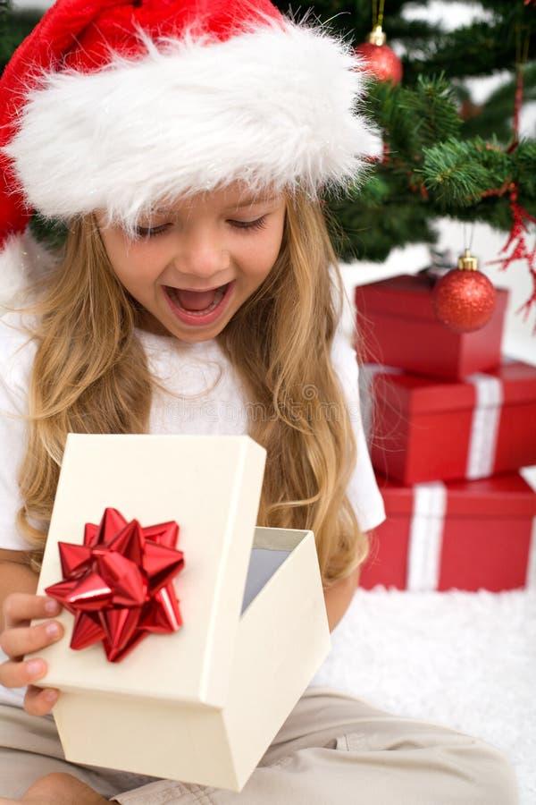 Aufgeregtes Öffnungs-Weihnachtsgeschenk des kleinen Mädchens stockfotografie