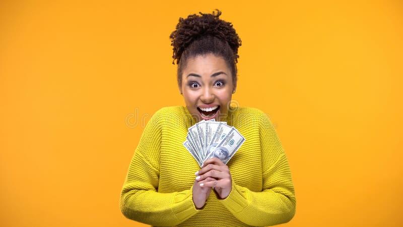 Aufgeregtes afroes-amerikanisch Frauenholdingbündel Dollar, Lottogewinner, Vermögen stockbild