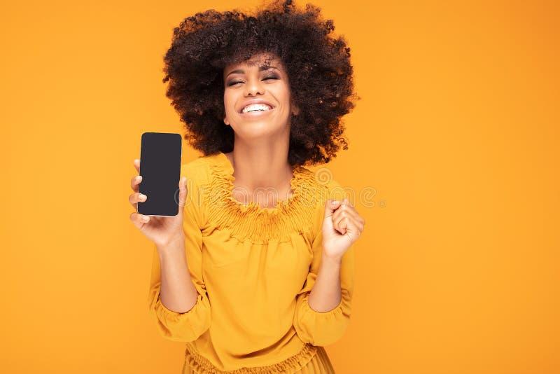 Aufgeregtes Afromädchen mit Handy lizenzfreie stockbilder