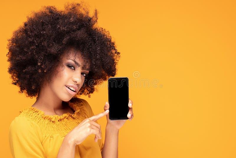 Aufgeregtes Afromädchen mit Handy lizenzfreie stockfotografie