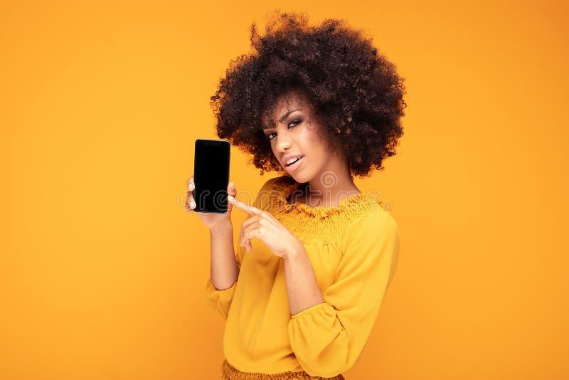 Aufgeregtes Afromädchen mit Handy stockfotografie