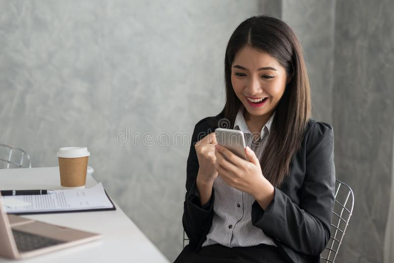 Aufgeregtes asiatisches Geschäftsmädchen beim Ablesen eines intelligenten Telefonsitzens lizenzfreie stockbilder