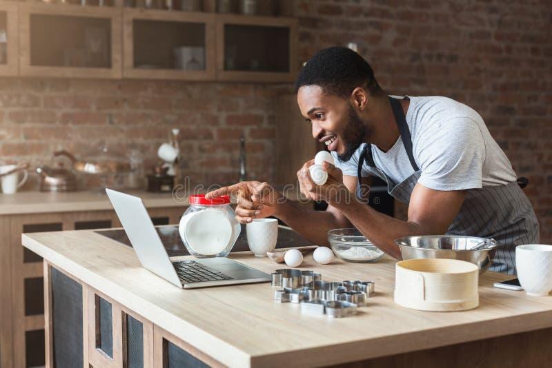 Aufgeregtes Backen des schwarzen Mannes und schauen Rezept auf Laptop stockfoto