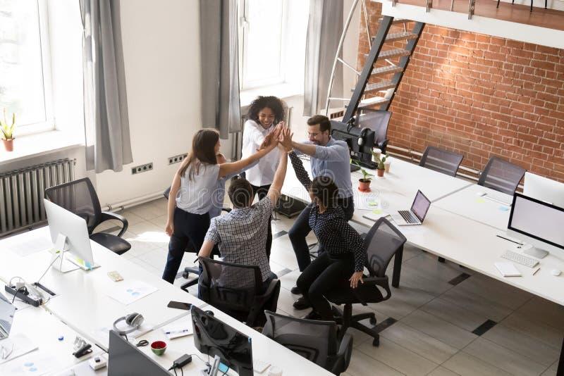 Aufgeregtes gemischtrassiges Büroangestelltteam, das zusammen hohe fünf gibt stockbilder