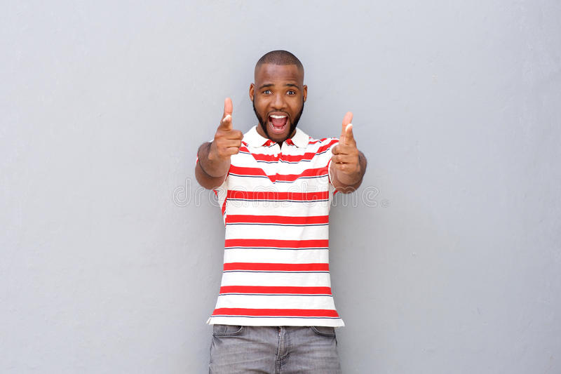 Aufgeregtes junges afrikanisches Mannzeigen lizenzfreies stockfoto