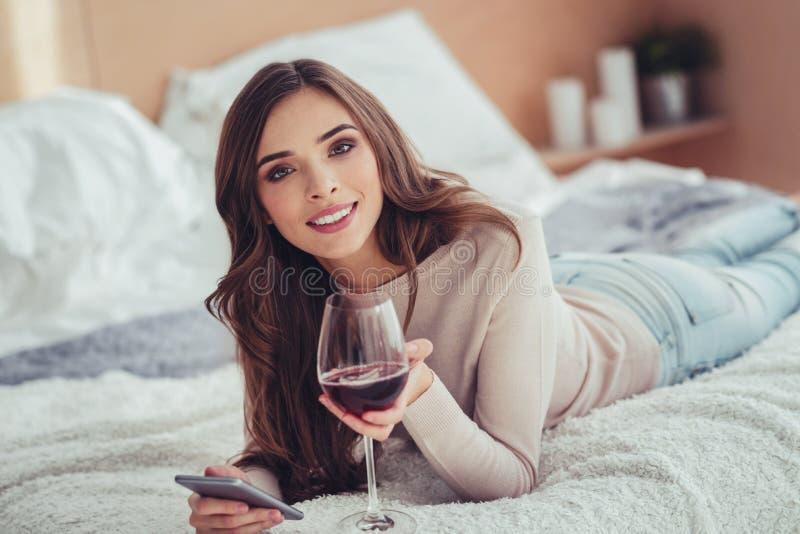 Aufgeregtes junges Mädchen, das auf dem Bett mit einem Glas Wein liegt lizenzfreies stockbild