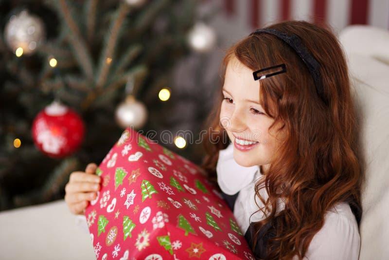 Aufgeregtes kleines Mädchen, das ein Weihnachtsgeschenk hält stockbild