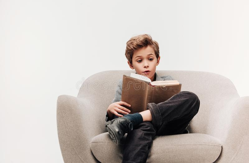 aufgeregtes kleines Schülerlesebuch im Lehnsessel stockbilder