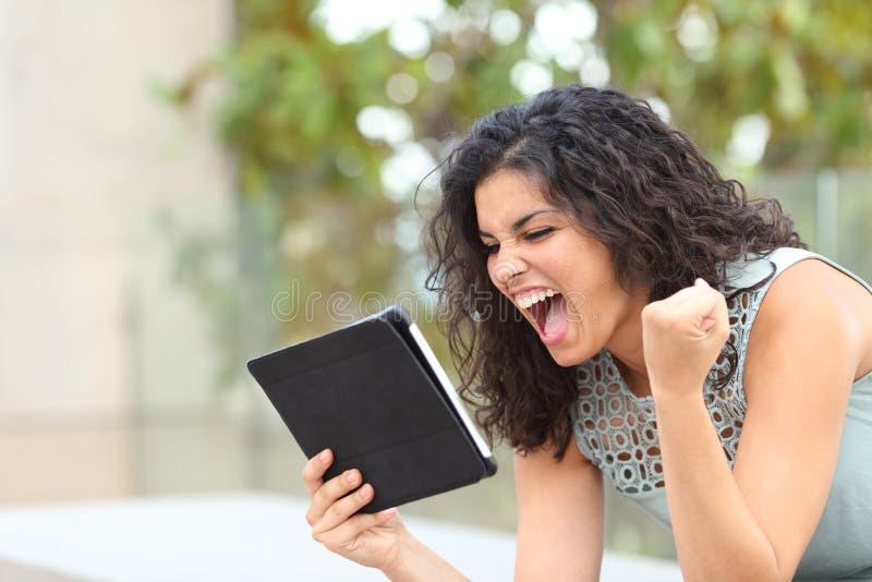 Aufgeregtes Mädchen, das eine Tablette hält und Nachrichten feiert stockfotos