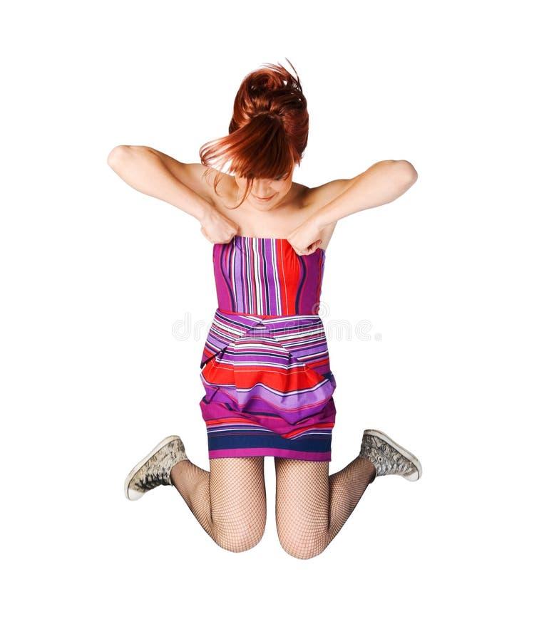 Aufgeregtes Mädchen, das hoch auf Weiß springt stockfotos