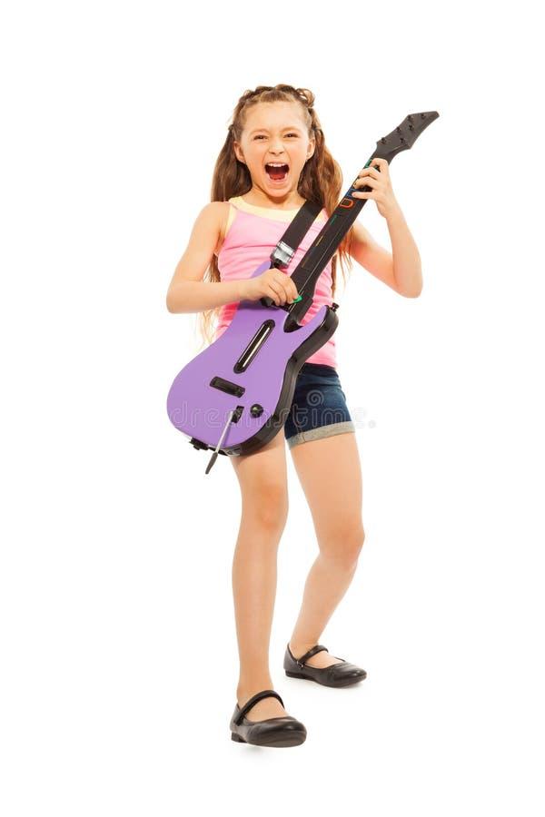 Aufgeregtes Mädchen mit dem langen Haar, das auf Gitarre spielt lizenzfreie stockfotos