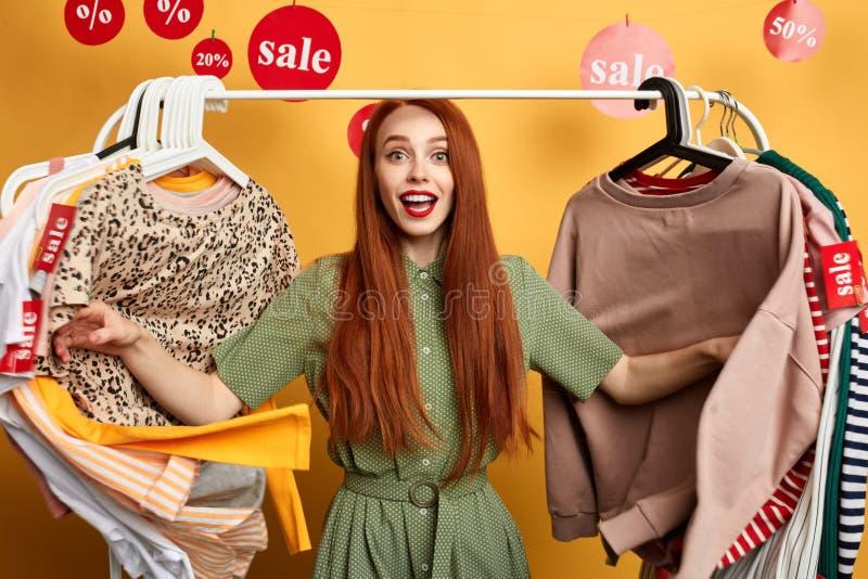 Aufgeregtes womna im grünen Kleid, das am Verkauf und an den Rabatten sich freut lizenzfreie stockbilder