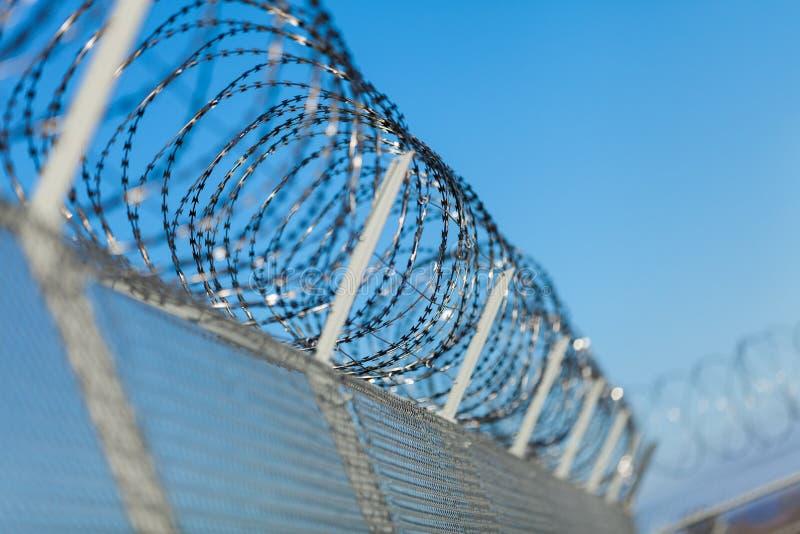 Aufgerollter Rasiermesserdraht auf einen Zaun lizenzfreie stockfotografie
