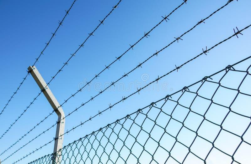 Aufgerollter Rasiermesserdraht mit seinen scharfen Stahlwiderhaken auf einen Maschenbegrenzungszaun, Sicherheit sicherstellend stockbilder