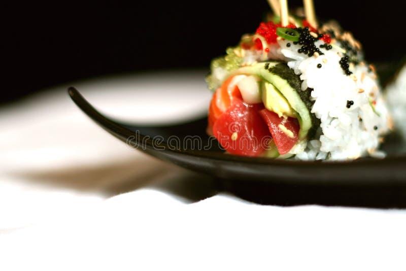 Aufgespigessene Sushi auf schwarzer Platte stockbild