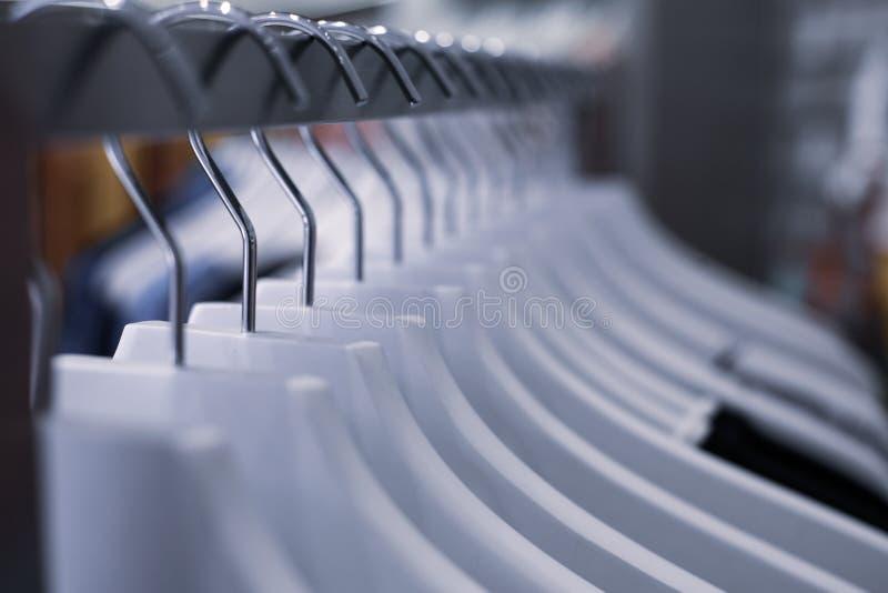 Aufhänger mit Kleidung auf dem Schaufenster im Speicher stockbild