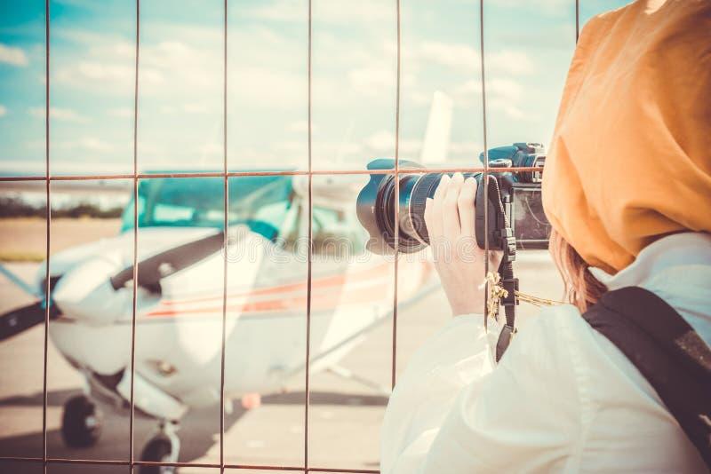 Aufklärer, der kleines Flugzeug durch den Zaun des Flughafens fotografiert lizenzfreie stockfotografie