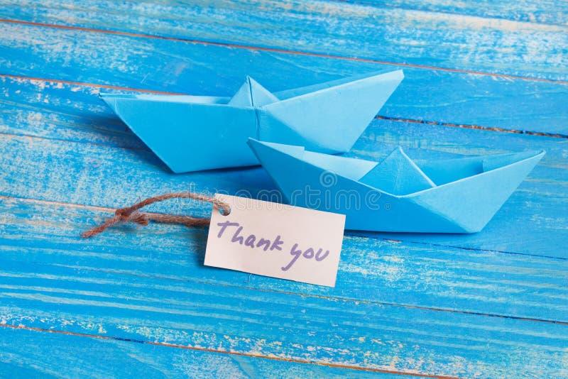 Aufkleber mit den Wörtern danken Ihnen Papierboot mit einem Zeichen lizenzfreie stockfotos