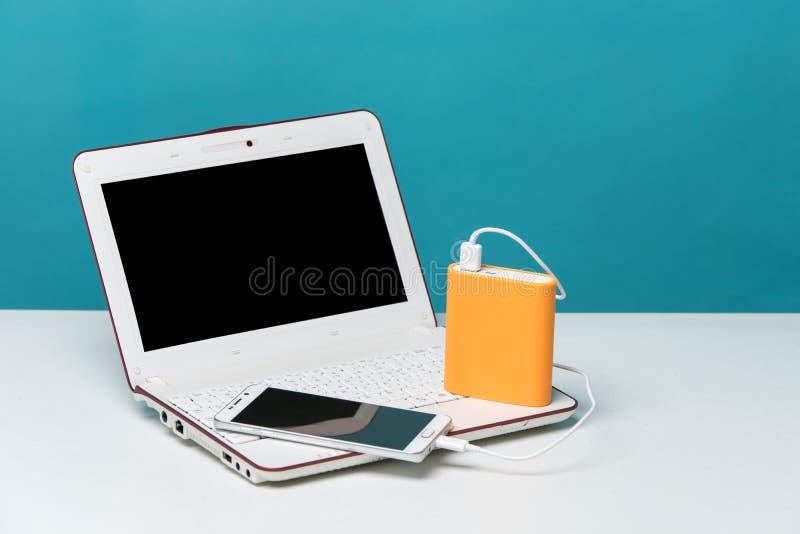Aufladendes intelligentes Telefon mit tragbarer externer Batterie auf modernem Laptop im Hintergrund stockfotografie